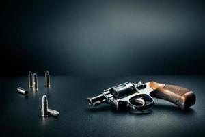 pistola sentada en una mesa con casquillos de bala foto