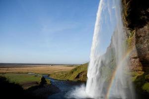 atrás da cachoeira Seljalandsfoss ao pôr do sol, sul da Islândia