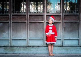 chica asiática en traje rojo de santa claus