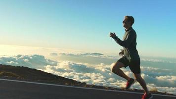 jovem correndo na estrada de montanha ao pôr do sol acima das nuvens. câmera lenta hd