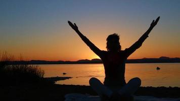 gesunde Frau, die bei Sonnenuntergang meditiert