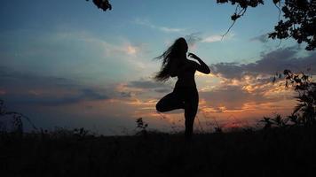 Silhouette female girl doing yoga background red sunset sky tree video