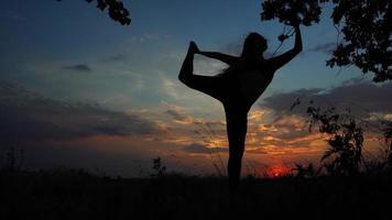 Silhouette female girl doing yoga background of sunset sky pose video