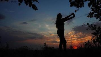 Silhouette female girl yoga background of sunset sky pose