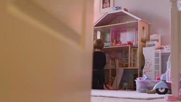 uma porta se abre para uma menina e sua mãe brincando com uma casa de boneca gigante em seu quarto, e então se fecha