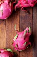 Four dragon fruits on a wooden table
