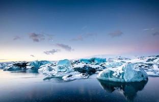Icebergs floating in Jokulsarlon glacier lake at sunset. South Iceland.