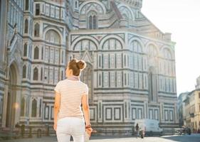 Young woman standing near cattedrale in florence photo