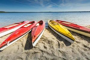 Colorful kayaks moored on lakeshore, Goldopiwo Lake, Mazury