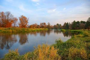 Autumn, river, grass and trees in fall colors photo