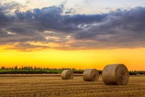 puesta de sol sobre caminos rurales y fardos de heno