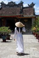Mujer vistiendo ao-dai afuera en Vietnam