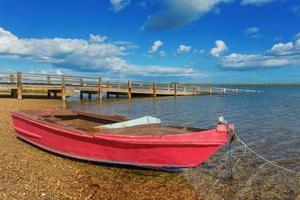 Red fishing boat on the shore. Near the bridge. photo