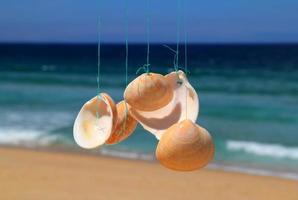 Seashell wind chime and beach. Portugal.