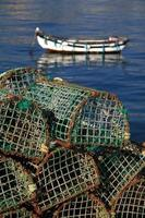 Fish traps with typical coastal fishing boat, Cascais Portugal.