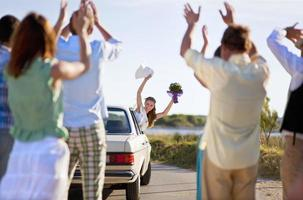 Bride waving to wedding party from car photo