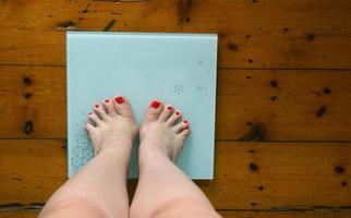 Woman weighing herself photo