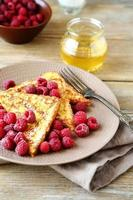 Tasty French toast with raspberries and honey