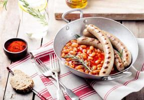 Grilled sausages with beans in tomato sauce