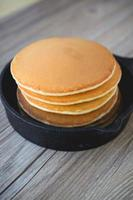 Stack of pancakes in frying pan with maple syrup
