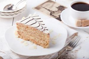Traditional Hungarian Esterhazy cake with coffee cup and vintage postcards