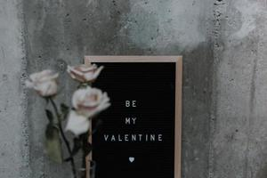 Pink flowers leaning against a board that says be my valentine