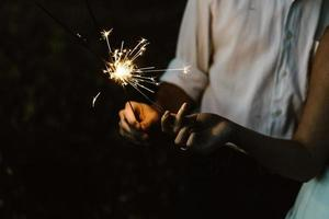 Two people holding sparklers together in the dark