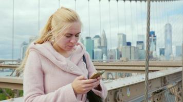 jovem digitando um sms em seu smartphone, em pé no parapeito da ponte de brooklyn em nova york