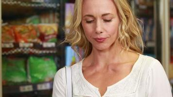 Pretty blonde checking grocery list video