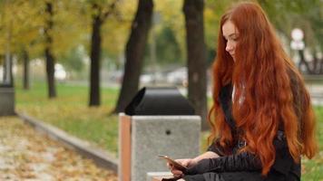 la niña mira y toca el teléfono, sentada en un banco en el día nublado de otoño.