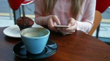 bella bionda che ha un caffè che scrive sul telefono