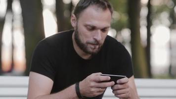 Close-up portrait séduisant jeune homme assis sur un banc dans le parc et à l'aide d'un smartphone