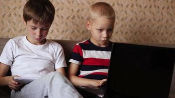 Two boys playing on  a tablet and a laptop at home sitting on the couch video