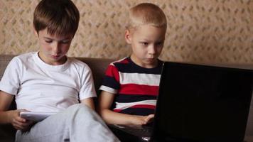 Zwei Jungen spielen auf einem Tablet und einem Laptop zu Hause und sitzen auf der Couch video