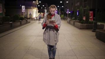 una niña se encuentra en el bulevar con una tableta por la noche. video