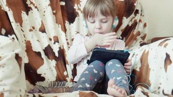 petite fille mignonne regarde des dessins animés sur l'onglet numérique