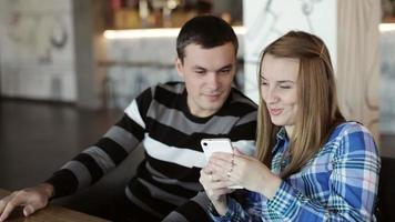 Woman and Man sitting in cafe talking and looking at phone in hand