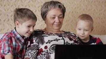 Kinder und Großmutter mit Laptop