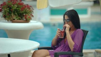 Young stylish beautiful woman drinking tropical cocktail near resort pool video