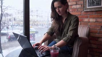 attraktive Frau, die auf dem Laptop in einem gemütlichen Café tippt