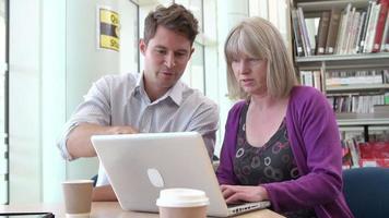 professor ajudando aluno maduro com estudos na biblioteca