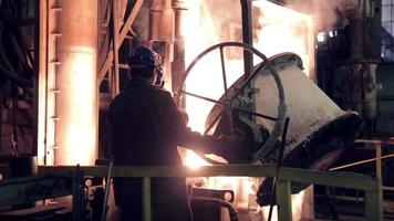 Worker on steel plant operates with  molten metal