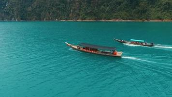 Aerial: Two long tail boats are on the lake.