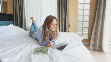 belle femme caucasienne travaillant sur ordinateur portable dans la chambre. jeune fille mignonne utilisant macbook et souriant. belle ado heureuse assise sur le lit et se prépare aux examens. matinée ensoleillée