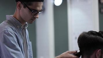 bell'uomo con la barba nel negozio di barbiere. barbiere che lavora con il rasoio elettrico. video