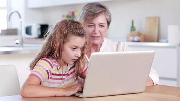 Kind mit Laptop mit ihrer Großmutter