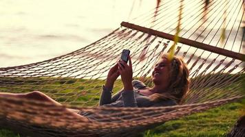 Young Woman Laughing Using Mobile Smart Phone while Relaxing in a Hammock by the Ocean Between Palm Trees at Sunset in Hawaii. video