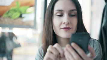 Beautiful woman using  smartphone in cafe video