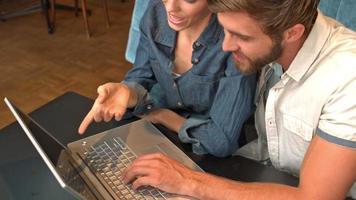 Linda pareja usando laptop en cafe