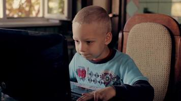 5 years old boy playing on  the computer at  home